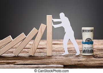 Paper Man Stopping Wooden Domino Blocks By Hundred Dollar Bills