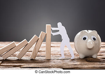Paper Man Stopping Wooden Domino Blocks By Piggy Bank