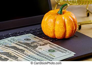 Paper money on laptop keyboard with pack twenty dollar bills