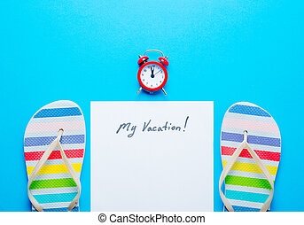 photo of sheet of paper My Vacation, red alarm clock and colorful sandals on hte wonderful blue studio background