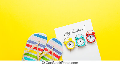 photo of sheet of paper My Vacation, colorful alarm clocks and colorful sandals on the wonderful yellow studio background