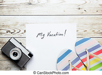 photo of sheet of paper My Vacation, retro camera and colorful sandals on the wonderful white wooden background