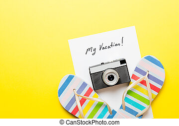 photo of sheet of paper My Vacation, retro camera and colorful sandals on the wonderful yellow studio background