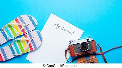 photo of sheet of paper My Vacation, retro camera in case and colorful sandals on hte wonderful blue studio background