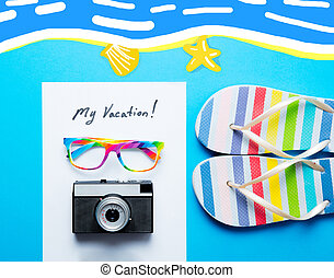 photo of sheet of paper My Vacation, colorful sandals, glasses and retro camera on the wonderful blue studio background