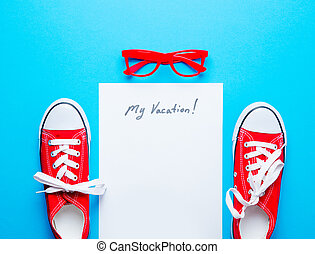 photo of sheet of paper My Vacation, red gumshoes and glasses on the wonderful blue studio background