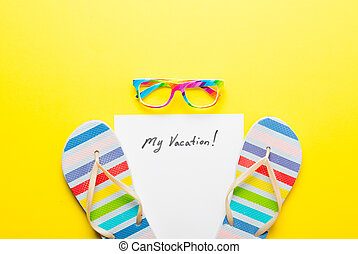 photo of sheet of paper My Vacation, colorful glasses and colorful sandals on the wonderful yellow studio background