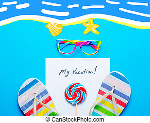 photo of sheet of paper My Vacation, lollipop, colorful sandals and glasses on the wonderful blue studio background