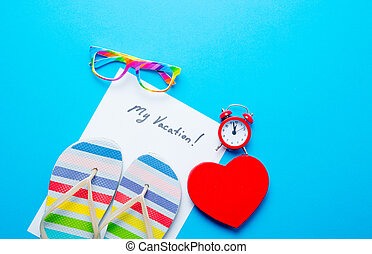photo of sheet of paper My Vacation, colorful sandals, alarm clock, glasses and heart shaped toy on the wonderful blue studio background