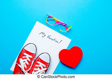 photo of sheet of paper My Vacation, colorful glasses, gumshoes and heart shaped toy on the wonderful blue studio background