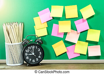 Paper note on chalk board with metal cup of pencils and alarm clock. Business table concept