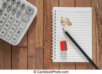 Paper note with pencil and calculator