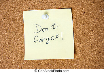 Paper note written with Don't Forget inscription on cork board