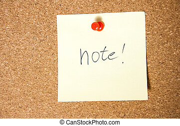 Paper note written with NOTE inscription on cork board.