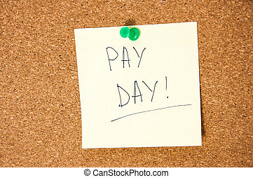 Paper note written with PAY DAY inscription on cork board.