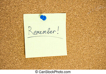 Paper note written with REMEMBER inscription on cork board.