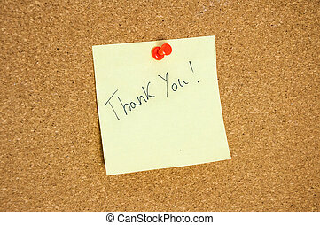 Paper note written with THANK YOU inscription on cork board.