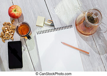 Paper notebook, pencil, cup of tea, apple, cellphone and walnuts on wooden table