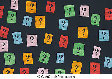 Paper notes with question marks on blackboard