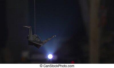 Paper origami crane hanging on thread against bright light...