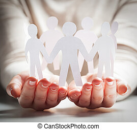 Paper people in hands in gesture of giving, presenting. Concept