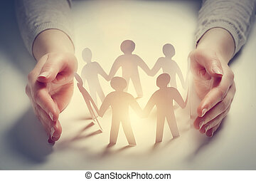 Paper people surrounded by hands in gesture of protection. Concept of insurance