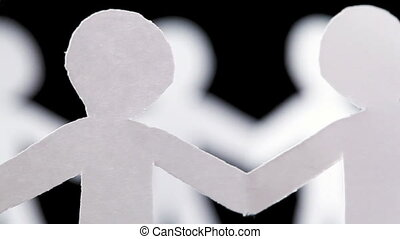 paper people waist-deep stand in circle and hold hands,...