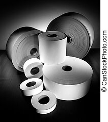 rolls of different sized paper on dark background in black and white