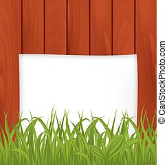 Paper sheet and green grass on wooden texture