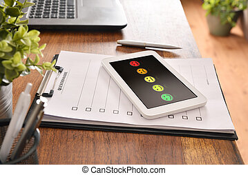 Paper sheet questionnaire and electronic device on a desk