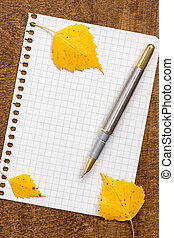 Paper sheet with pen and autumnal leaves