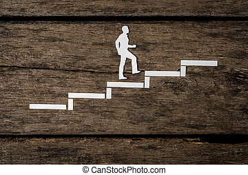 Paper silhouette cutout of a man climbing the stairs