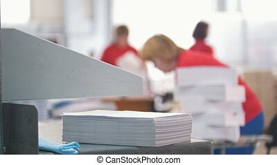 Paper stack in front of women working in typography -...