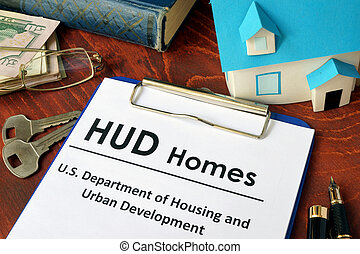 Paper with words HUD homes on a wooden surface.