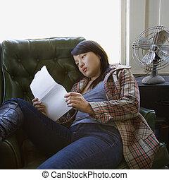 paper., woman olvas