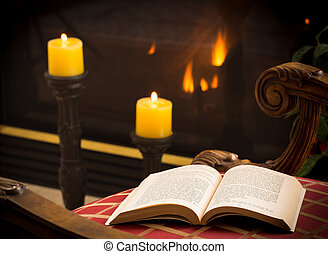 Paperback book open on chair by fire and candle - James...