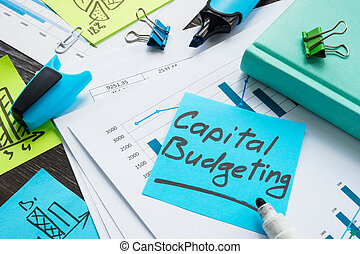Papers with capital budgeting and business charts.