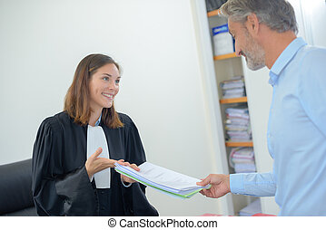 Paperwork being passed between lawyer and client