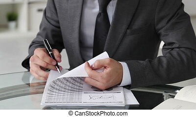 Businessman looking through documents and making notes