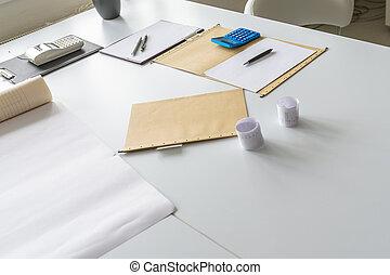Paperwork, calculator and folders on an office desk