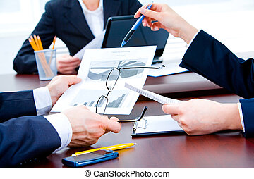 Paperwork - Closeup of business partners� hands holding...