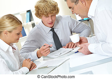 Paperwork - Portrait of three businesspeople discussing plan...