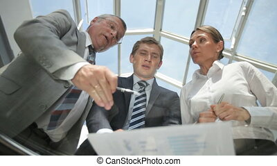 Serious business people viewed from below discussing financial data