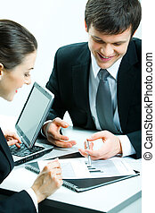 Paperwork - Vertical image of two business partners looking...