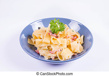 Pappardelle Carbonara on a blue plate on a white background