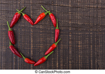Paprika red pepper in the shape of heart. The texture on a wooden background. Valentine's Day.