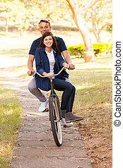 par adolescente, ande uma bicicleta