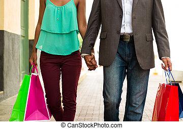 par americano africano, shopping, com, sacolas, em, cidade...