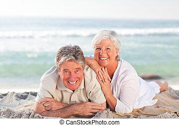 par ancião, deitando-se, praia