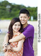 par asiático, sorrindo